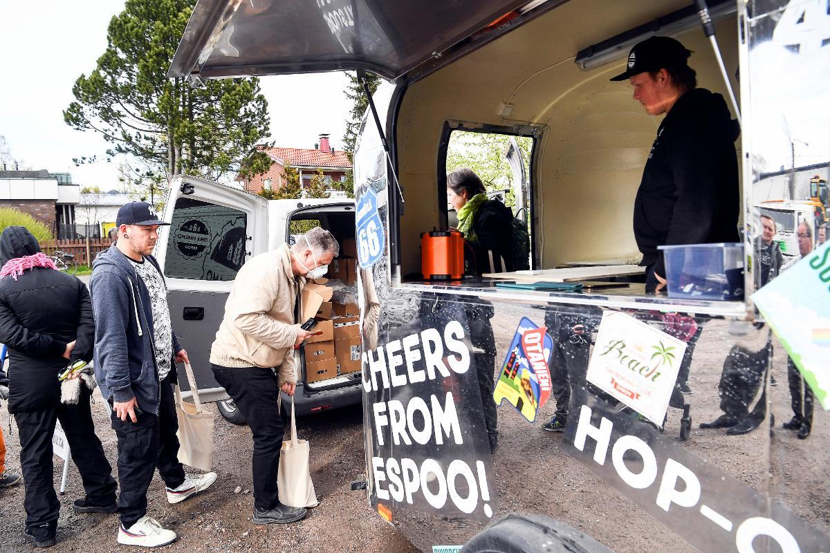 People queue in front of a mobile trailer selling local beer in Espoo. The Oma Panimo microbrewery came up with a new way to boost beer sales during the lockdown. Kuva: epa08422298